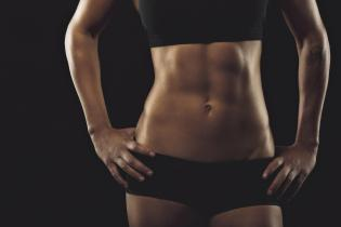 Close up of fit woman's torso with her hands on hips. Female with perfect abdomen muscles on black background