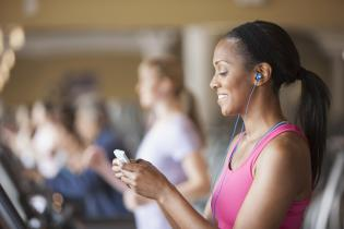 African American woman using cell phone in gym
