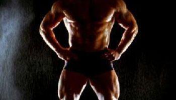 Medium shot tilt up portrait of shirtless muscular man with hands on hips / mist falling in background