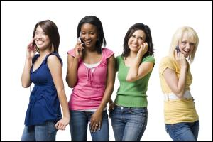Four women talking on cell phones smiling