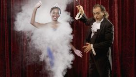 Magician making woman appear out of thin air