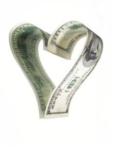 Hundred dollar banknote forming heart shaped reflection, close-up