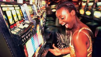 Young woman winning money from slot machine, profile