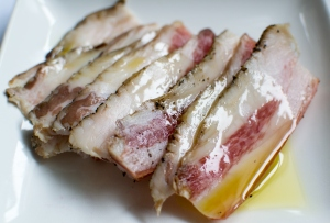 Close up of delicious delicate fatty cooked bacon with oil on plate