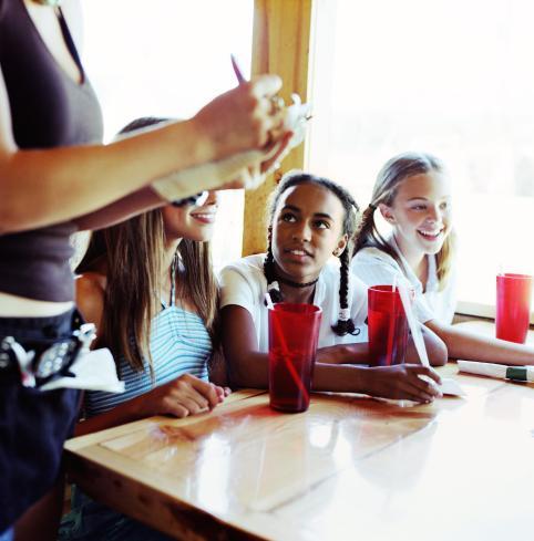 Teenage girls (14-16) giving waitress order in diner