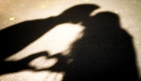 Silhouette of two lovers. Kissing and forming a heart shape.