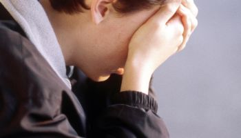 depressed teenager sitting with head in hands