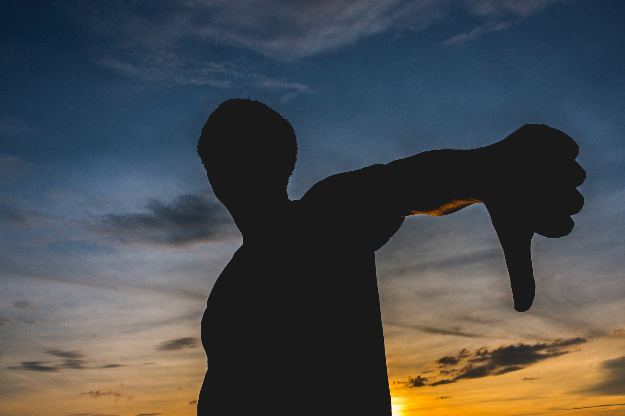 Silhouette Man Gesturing Thumbs Down Against Sky During Sunset