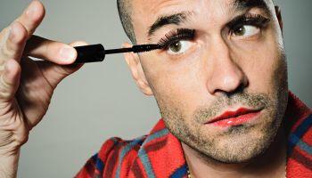 Young Man Applying False Eyelashes and Mascara