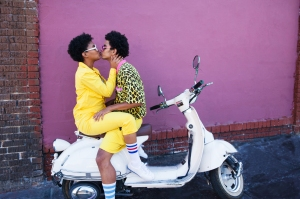 Young couple kissing on the back of a scooter