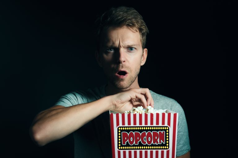 Portrait Of Surprised Man Eating Popcorn Against Black Background