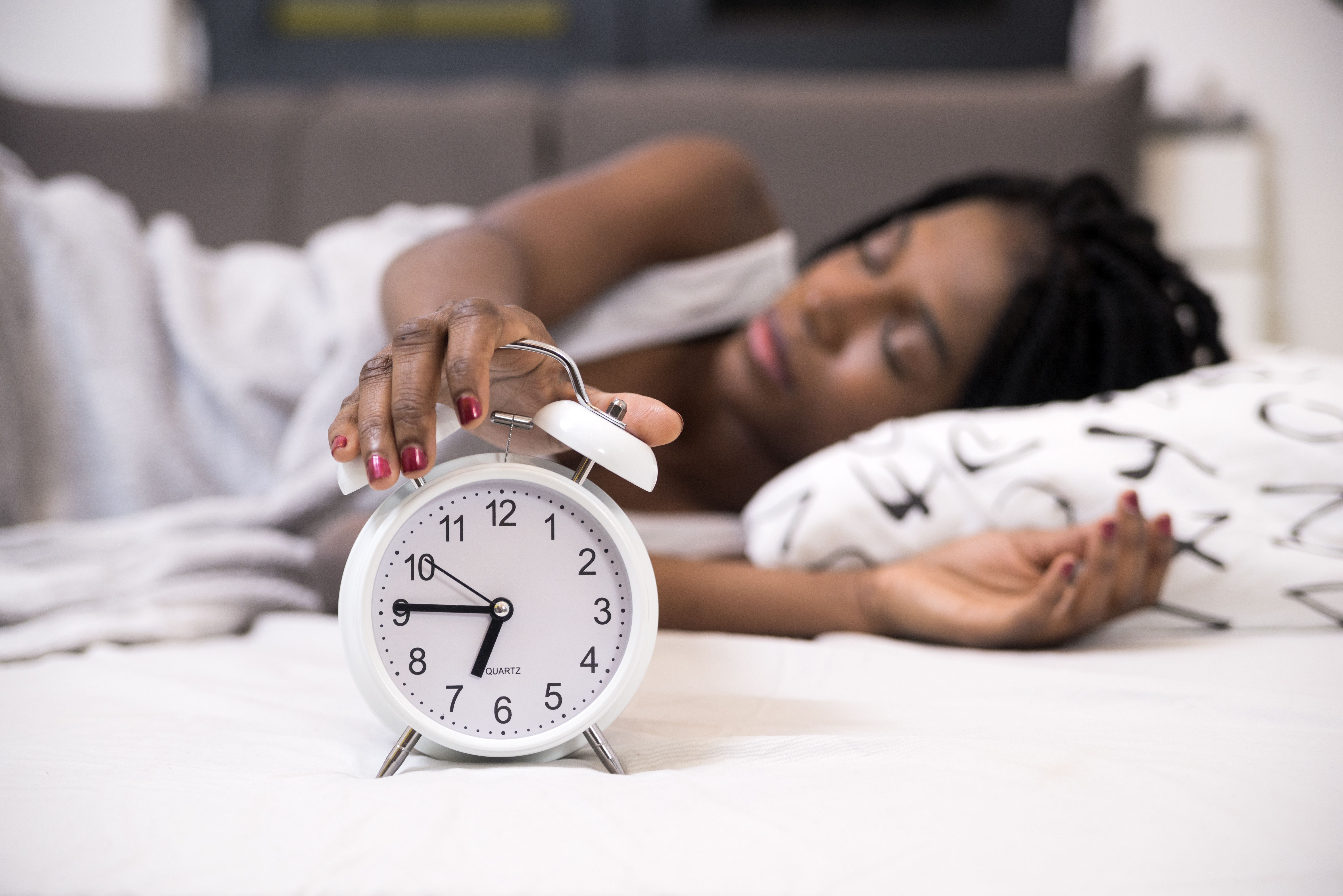 Tired woman switching off her alarm clock in her bedroom