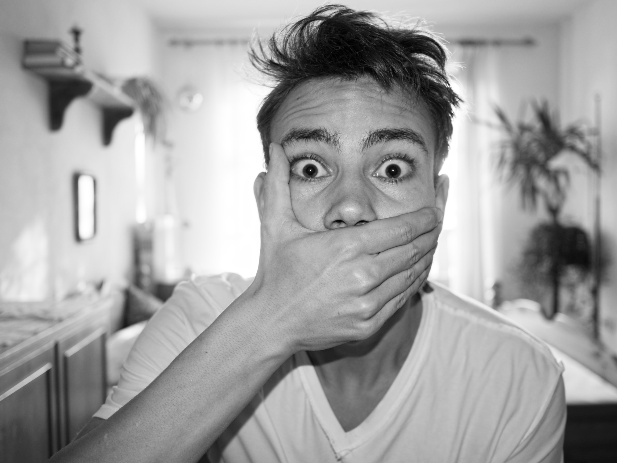 Portrait Of Shocked Man Covering Mouth At Home