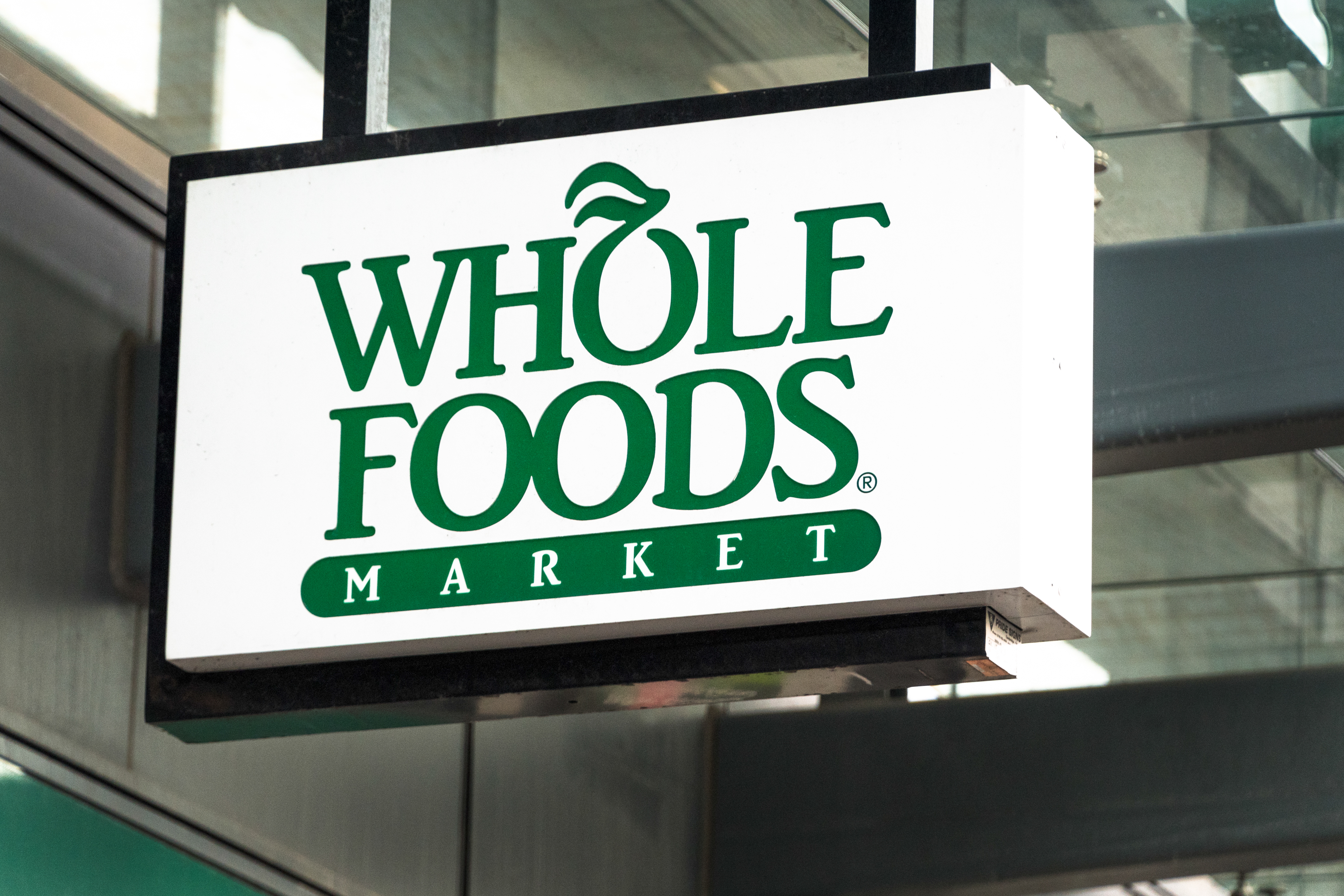 Whole Foods sign hanging on a store entrance in Yonge Street...