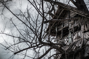 Scary looking wooden tree house under stormy sky