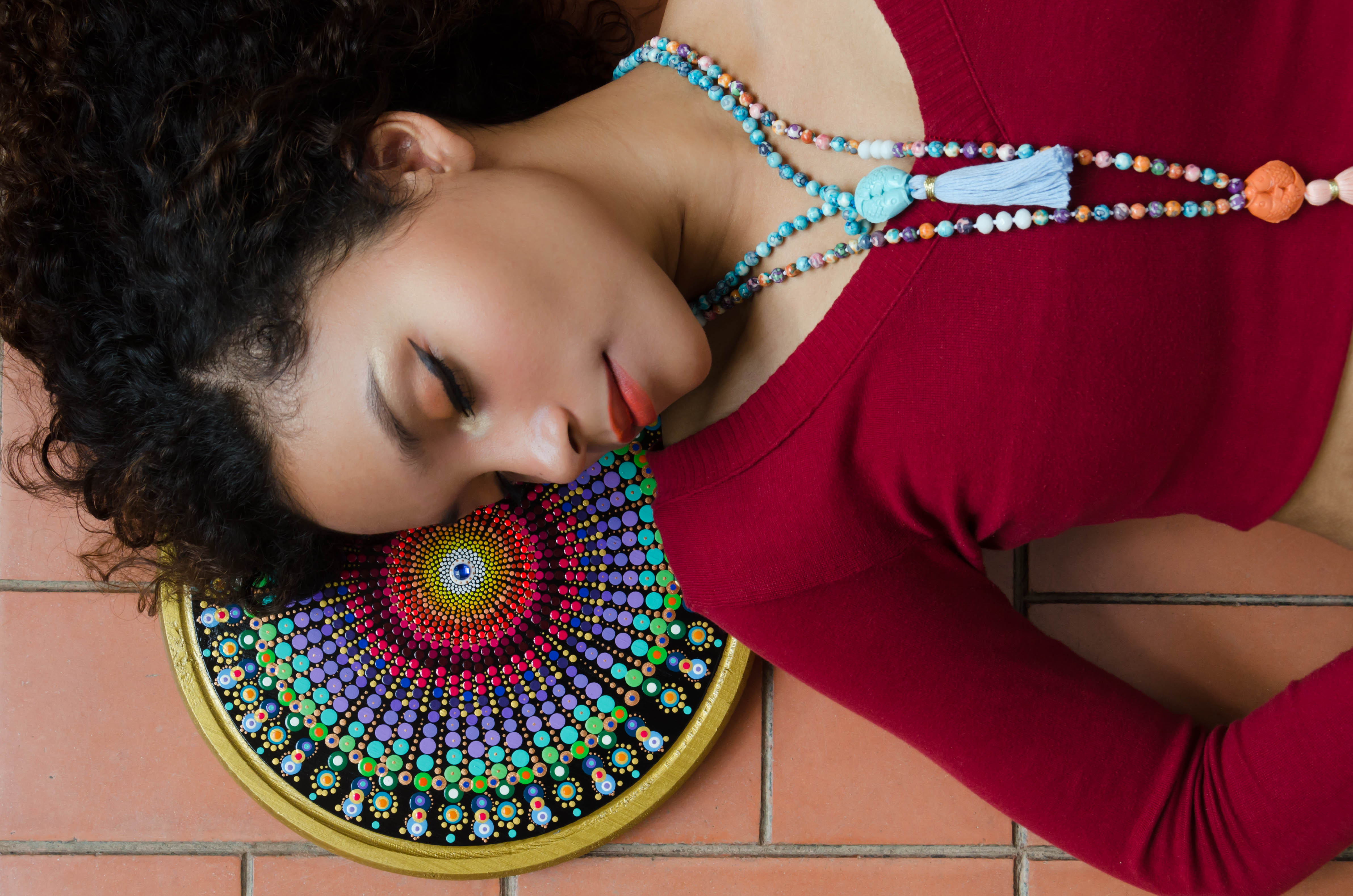 Beautiful hispanic woman lying down, her head resting on a mandala