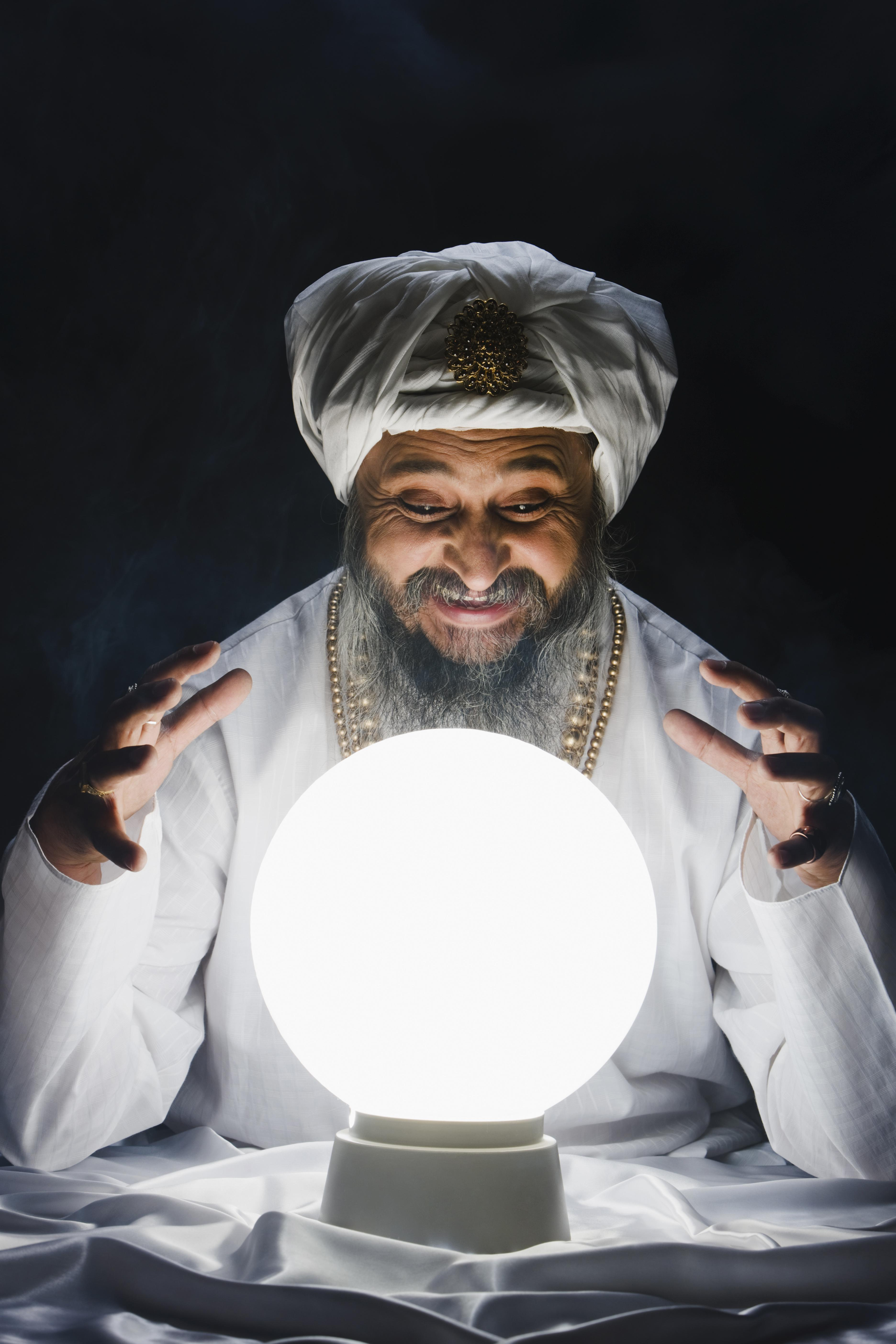 Male fortune teller and crystal ball