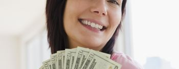 Young woman holding money, smiling