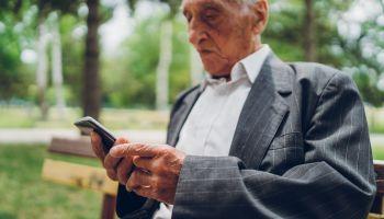 Senior man using phone in a park