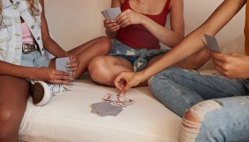 Young women playing cards in bunk bed, at youth hostel