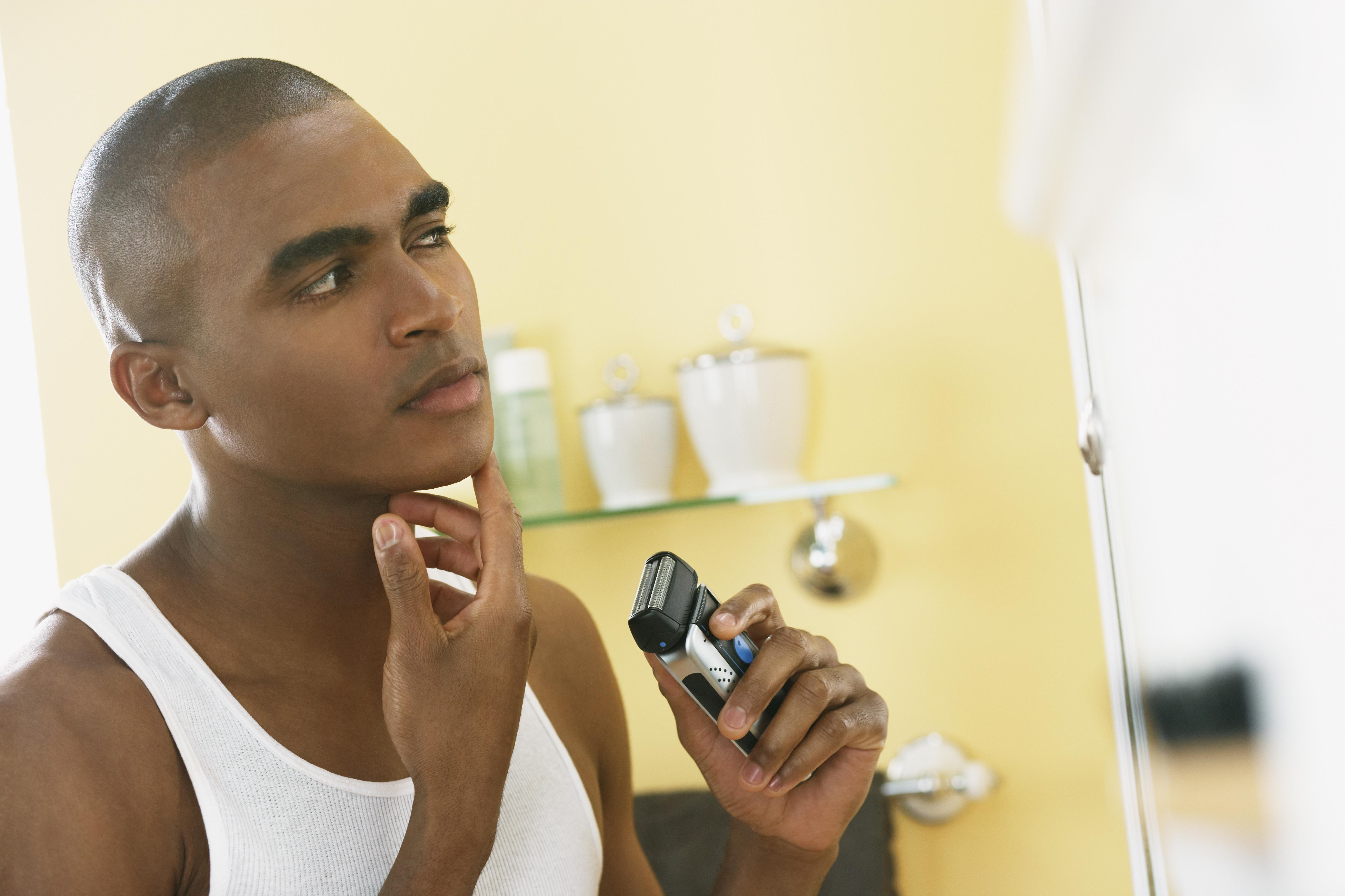 African man shaving with electric razor