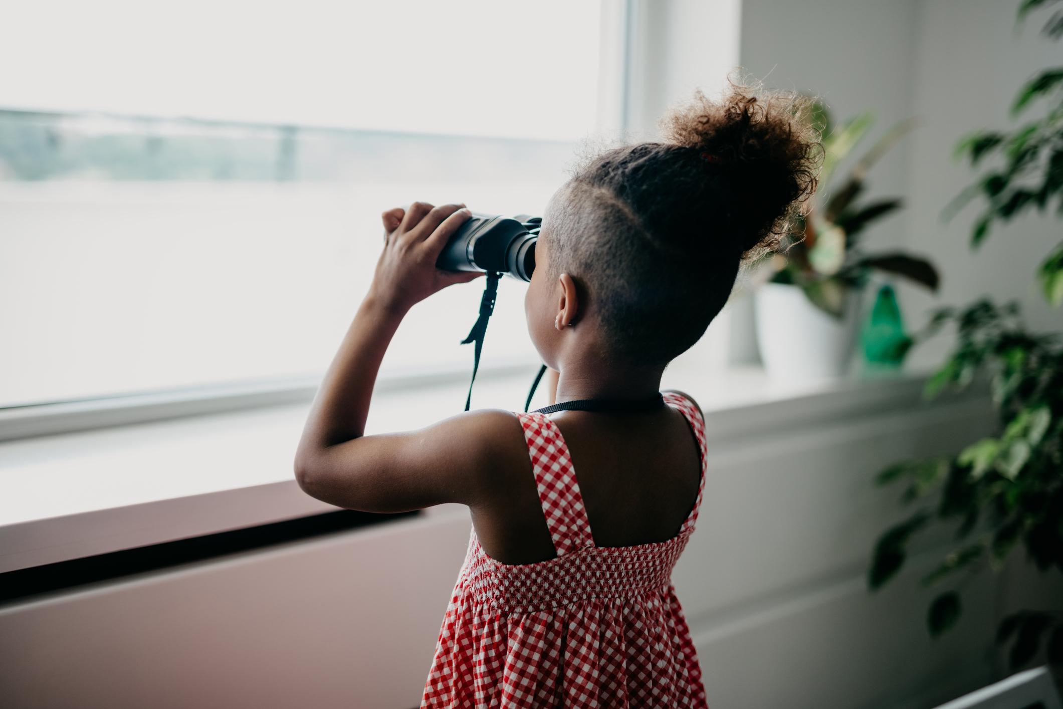 Rear view at african kid looking through binoculars