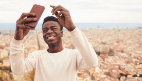 Happy man taking selfie through phone against city