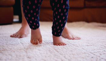 Low Section Of Mother And Baby Girl Walking On Rug At Home
