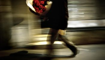 A man carries a bouquet of red roses dur