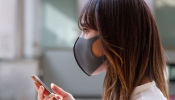 A woman wearing a face mask as a preventive measure walks on...